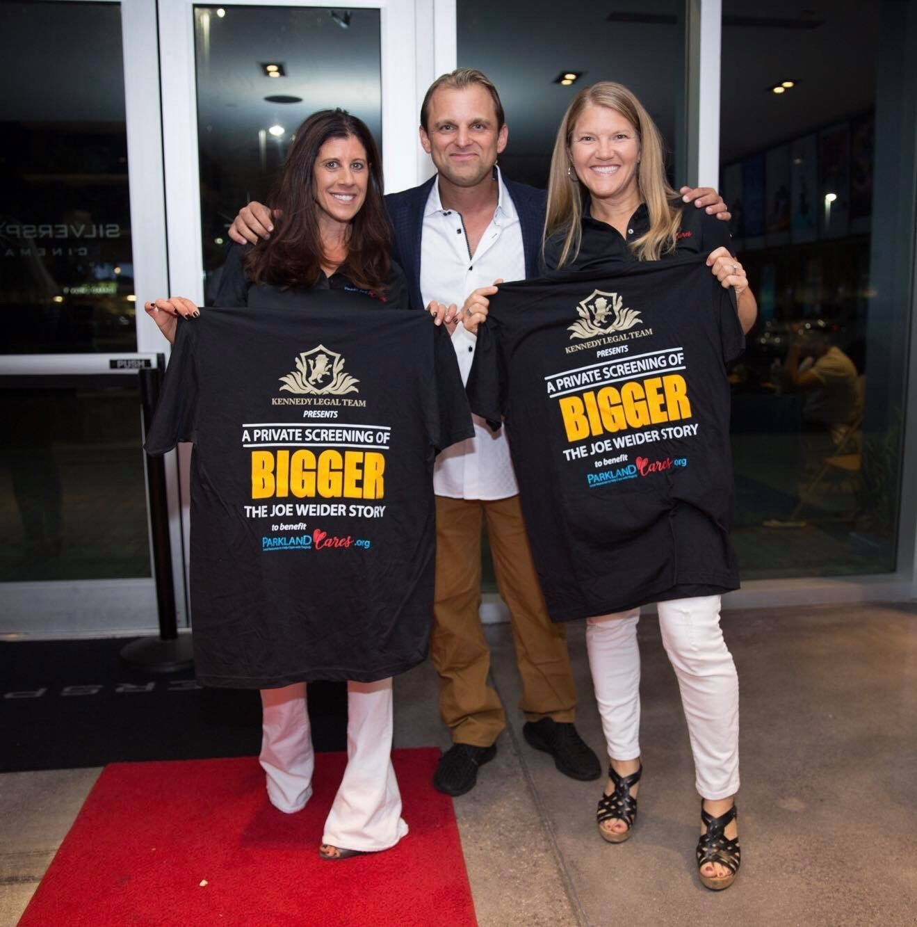 Pam and Stacy holding up BIGGER event T-shirts with Dan Solomon