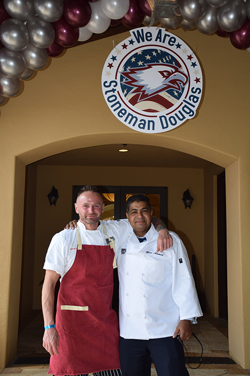 Two chefs embracing in front of We Are Stoneman Douglas banner
