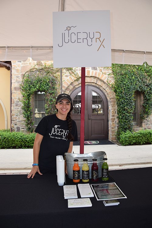 Employee and her juices at the JuiceryRx stand