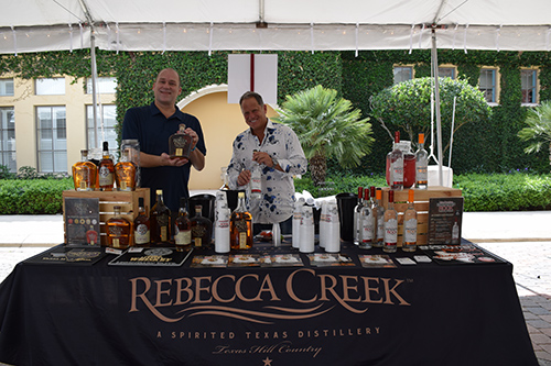 Two men posing with bottles behind Rebecca Creek Distillery stand