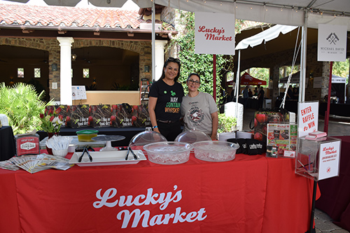 Two employees in front of Lucky's Market stand