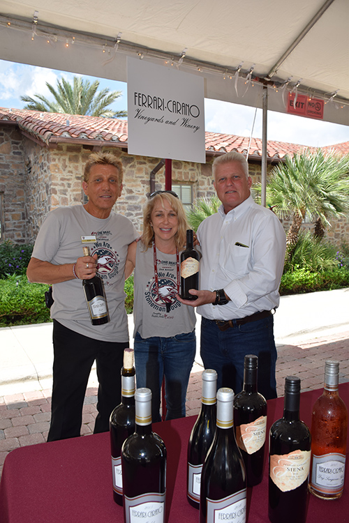 Three employees posing with wines at the Ferrari Carano Vineyards and Winery stand