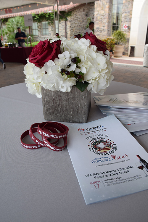 Table decorated with flowers, Parkland Cares bracelets, and brochure from the One Beat CPR + AED 2nd annual We Are Stoneman Douglas event