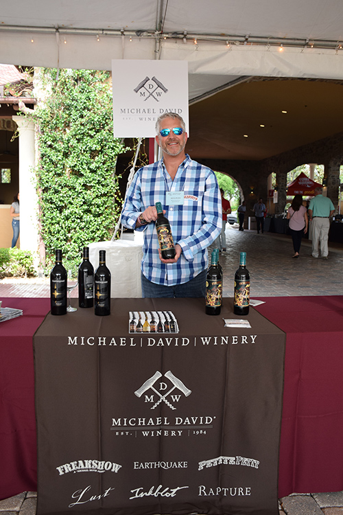 Man holding wine bottle behind Michael David Winery stand