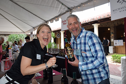 Smiling couple with wines in hand