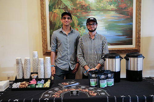 Two men serving coffee at stand
