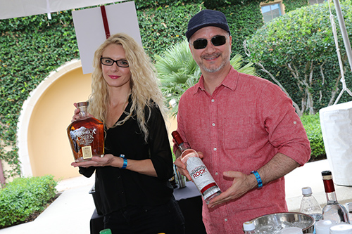 Couple posing with liquor bottles