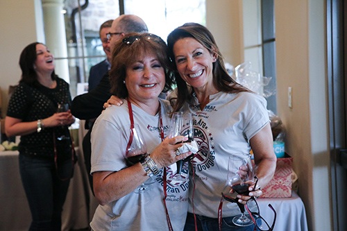 Two women enjoying wine at the One Beat CPR + AED 2nd annual We Are Stoneman Douglas event