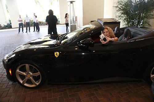 Christine posing inside a Ferrari